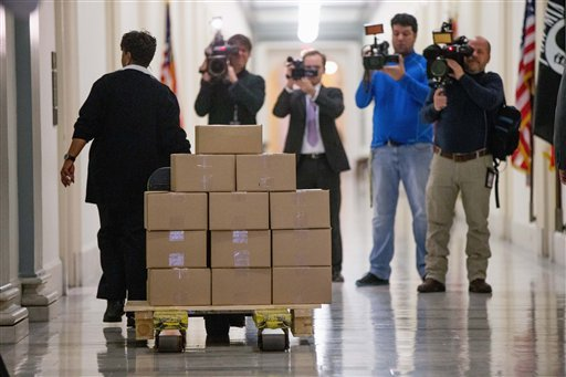 A staff member delivers President Barack Obama's fiscal 2017 federal budget to the House Budget Committee Room on Capitol Hill in Washington, Tuesday, Feb. 9, 2016.