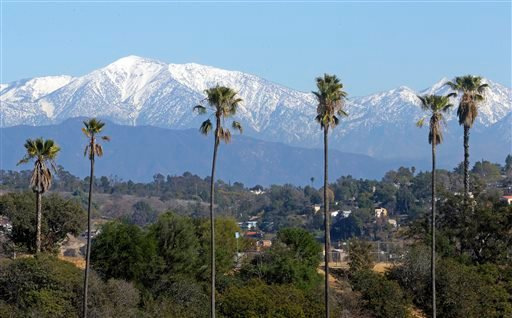 This Jan. 12, 2016 file photo shows the snow-capped San Gabriel Mountains, with Mount Baldy the highest peak at the left, seen from Chinatown near downtown Los Angeles. Authorities have closed trails at Baldy following the death of the second hiker in a w