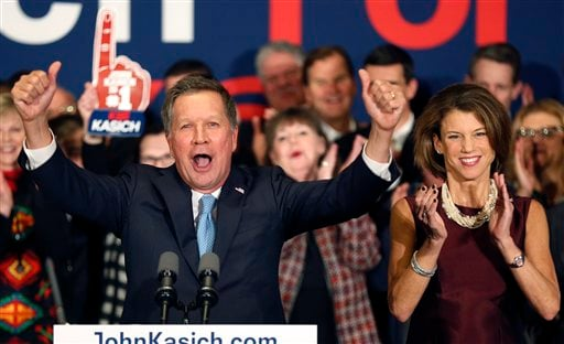 With his wife Karen at his side Republican presidential candidate Ohio Gov. John Kasich cheers with supporters Tuesday, Feb. 9, 2016, in Concord, N.H., at his primary night rally.