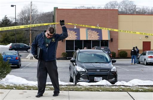 An investigator walks beneath a police tape line at the scene of a shooting at a shopping center in Abingdon, Md., Wednesday, Feb. 10, 2016. A man opened fire inside a shopping center restaurant during lunchtime. (AP Photo/Patrick Semansky)