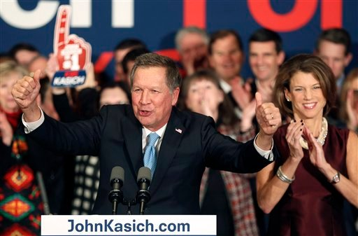 With his wife Karen at his side Republican presidential candidate Gov. John Kasich, R-Ohio, cheers with supporters Tuesday, Feb. 9, 2016, in Concord, N.H. , at his primary night rally. (AP Photo/Jim Cole)