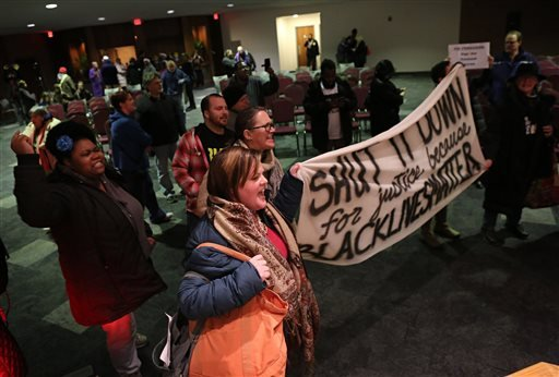 Protesters chant and yell after the Ferguson, Mo., city council meeting in Ferguson on Tuesday, Feb. 9, 2016, where the council voted to approve a modified consent decree with the United States Department of Justice. It is unclear if the Department of Jus