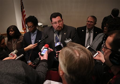 Ferguson mayor Mayor James Knowles III, center, talks to the media after the Ferguson, Mo., city council meeting in Ferguson on Tuesday, Feb. 9, 2016, where the council voted to approve a modified consent decree with the United States Department of Justic