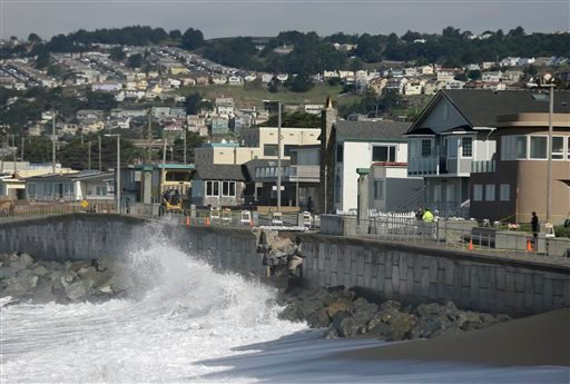 In this file photo from Monday, Jan. 25, 2016, waves crash near a damaged section of seawall in Pacifica, Calif.