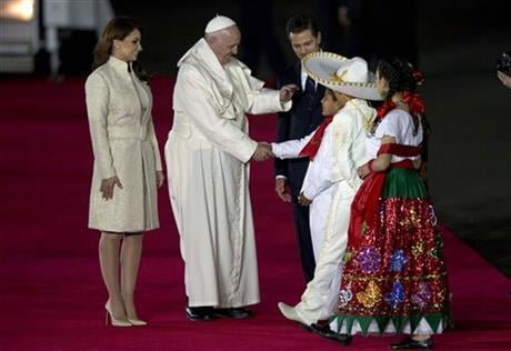 Pope Francis, center, greets youth dressed in traditional Mexican outfits as he's escorted by Mexico's President Enrique Pena Nieto, behind, and first lady Angelica Rivera, upon arrival to Benito Juarez International Airport in Mexico City. (AP Photo)
