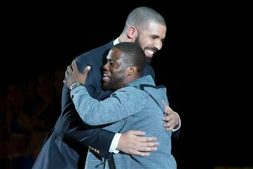 Canada coach Drake, left, hugs U.S. plyer Kevin Hart at the Celebrity Game, part of NBA basketball's All-Star weekend, in Toronto, Friday, Feb. 12, 2016.