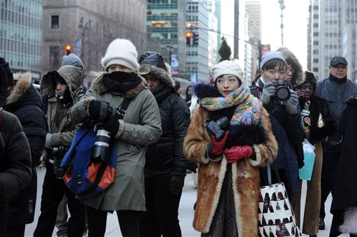 Street photographers brave the cold to photograph guests arriving to the Alexander Wang Fall 2016 show during Fashion Week, Saturday, Feb. 13, 2016, in New York. With temperatures continuing to drop throughout the day Saturday, Mayor Bill de Blasio urged