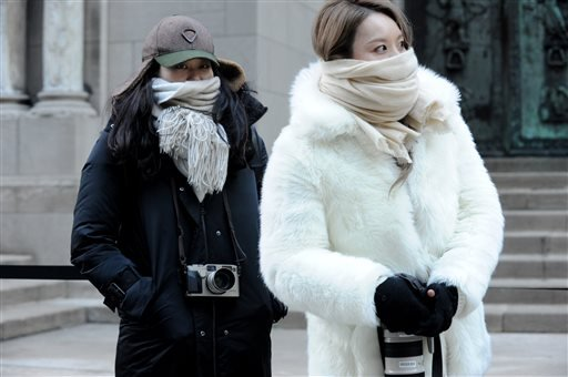 Street photographers brave the cold to photograph guests arriving to the Alexander Wang Fall 2016 show during Fashion Week, Saturday, Feb. 13, 2016, in New York. Bitter temperatures and biting winds had much of the northeastern United States bundling up f