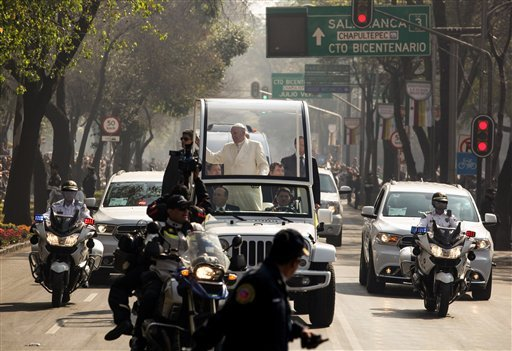 Police escort Pope Francis as he makes his way through one of Mexico City's main avenues on the popemobile, Sunday, Feb. 14, 2016, 2016. Pope Francis will give a Mass at an outdoor field in the capital's suburb of Ecatepec to an estimated crowd of 400,000