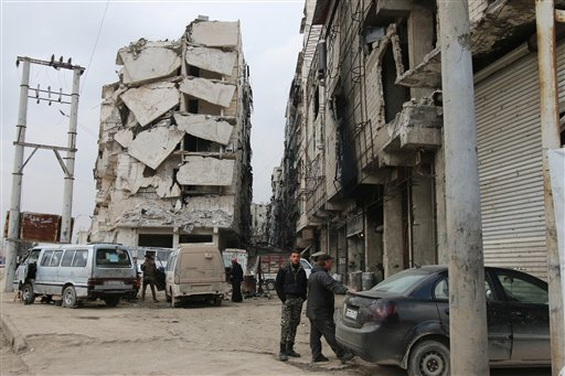 In this Thursday, Feb. 11, 2016 photo, a building is seen with heavy damage in Aleppo, Syria. The fighting around Syria's largest city of Aleppo has brought government forces closer to the Turkish border than at any point in recent years, routing rebels f
