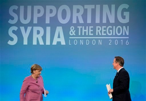 In this file photo dated Thursday, Feb. 4, 2016, British Prime Minister David Cameron, right, walks back to his seat on the stage after speaking, as German Chancellor Angela Merkel gets up for her turn to speak during a press conference near the end of th