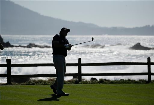 Phil Mickelson is silhouetted while hitting from the 18th tee of the Pebble Beach Golf Links during the third round of the AT&T Pebble Beach National Pro-Am golf tournament Saturday, Feb. 13, 2016, in Pebble Beach, Calif. (AP Photo/Eric Risberg)