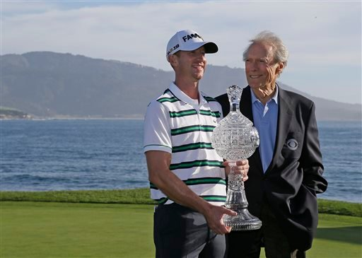 Vaughn Taylor, left, poses with his trophy and Clint Eastwood, right, on the 18th green of the Pebble Beach Golf Links after winning the AT&T Pebble Beach National Pro-Am golf tournament Sunday, Feb. 14, 2016, in Pebble Beach, Calif. Taylor won the tourna