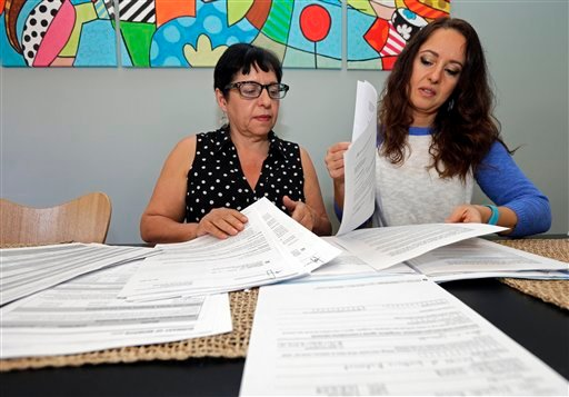 Ana Granado, left, and her daughter Andreia Walker, right, look over healthcare paperwork at their home in Charlotte, N.C., Wednesday, Feb. 10, 2016. (AP Photo/Chuck Burton)