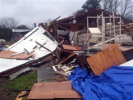 Area residents survey damage to a business off Mississippi Highway 18 in Sylverana, Miss., Monday, Feb. 15, 2016, after severe weather affected south Mississippi.