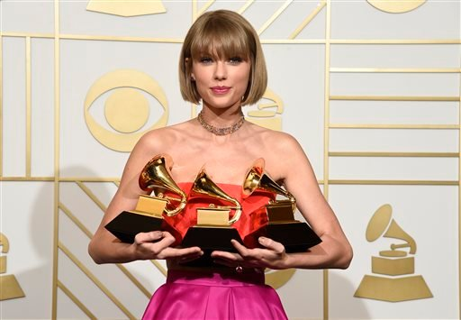 "Taylor Swift poses in the press room with the awards for album of the year for 1989, pop vocal album for 1989 and best music video for ""Bad Blood"" at the 58th annual Grammy Awards at the Staples Center on Monday, Feb. 15, 2016, in Los Angeles."