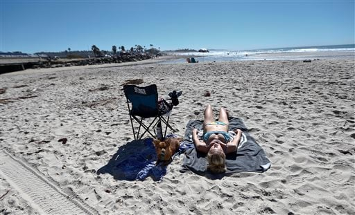 Kim McIntyre, from La Jolla, Calif., along with her dog Benji rest on the beach in Encinitas, Calif., Tuesday, Feb. 16, 2016.