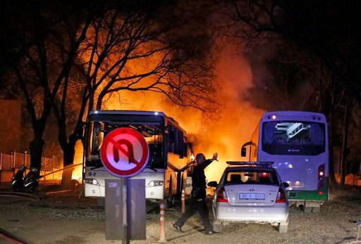 A police officer clears the area of an explosion in Ankara, Wednesday, Feb. 17, 2016, after assailants exploded a car bomb near vehicles carrying military personnel in the Turkish capital, killing several people and injuring scores of others, officials sa