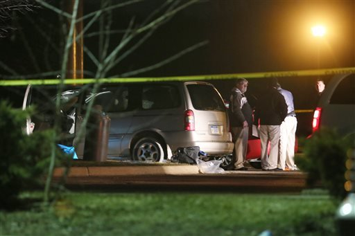 Police investigate the scene early Sunday, Feb. 21, 2016, where people were shot in vehicles outside a Cracker Barrel restaurant in Kalamazoo, Mich. A man drove around Kalamazoo shooting people at three locations Saturday, leaving six dead and three injur