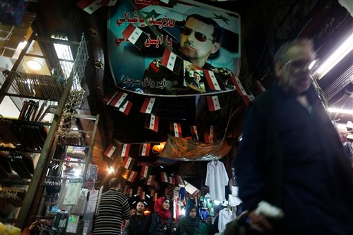 A Syrian walks under a poster of the Syrian President Bashar Assad at the popular Hamidiyeh old market in Damascus , Syria, Sunday, Feb. 21, 2016. The Islamic State group claimed responsibility for a triple blast in Sayyida Zeinab, a Shiite suburb of Dama