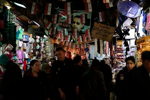Syrian walk under a poster of the Syrian President Bashar Assad and Syrian national flags at the popular Hamidiyeh old market in Damascus , Syria, Sunday, Feb. 21, 2016. The Islamic State group claimed responsibility Sunday for a triple blast in a Shiite