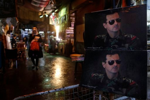 Pictures of the Syrian President Bashar Assad are seen at a check point on one of the entrances to the popular Hamidiyeh old market in Damascus , Syria, Sunday, Feb. 21, 2016. The Islamic State group claimed responsibility for a triple blast in Sayyida Ze