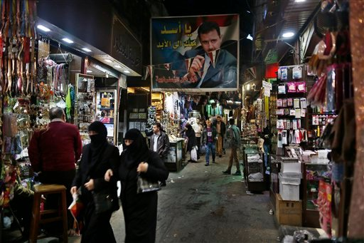 "A poster of the Syrian President Bashar Assad with Arabic reads, ""Assad we are with you for ever "" hangs up at the popular Hamidiyeh old market in Damascus , Syria, Sunday, Feb. 21, 2016. (AP Photo/Hassan Ammar)"