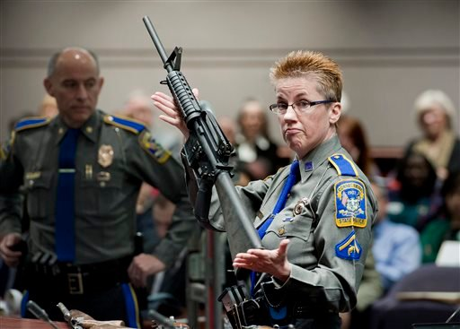 Jan. 28, 2013, file photo, firearms training unit Detective Barbara J. Mattson, of the Connecticut State Police, holds up a Bushmaster AR-15 rifle, the same make and model of gun used by Adam Lanza in the Sandy Hook School shooting. (AP Photo/Jessica Hill