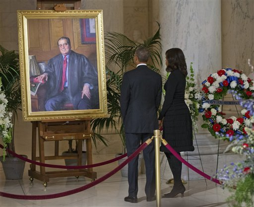 President Obama and first lady Michelle Obama stop to look at a portrait of Supreme Court Justice Antonin Scalia after paying their respects at Scalia's casket in the Great Hall of the Supreme Court Feb. 19, 2016. (AP Photo/Pablo Martinez Monsivais)
