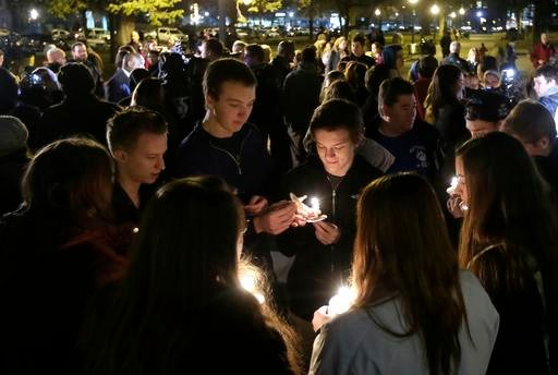 People gather in Bronson Park in Kalamazoo, Mich., Monday, Feb. 22, 2016, for a candlelight vigil for the victims of a series of random shootings in the Kalamazoo area over the weekend.