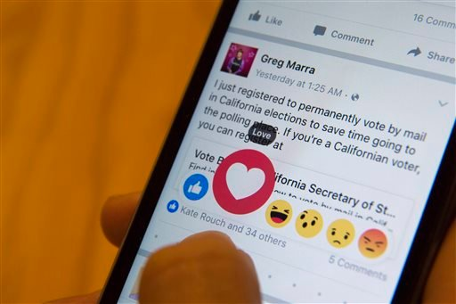 Feb. 18, 2016 photo (New York): Julie Zhuo, product design director at Facebook, demonstrates new emoji-like stickers customers will be able to press in addition to the like button. (AP Photo/Mary Altaffer)