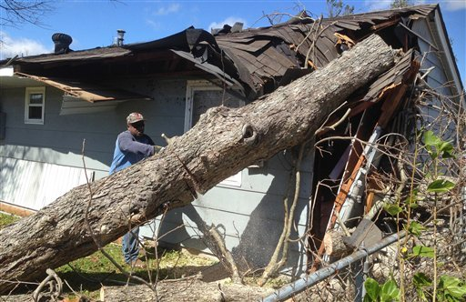 Alvin Guillard, of Laplace, La., cuts a tree that has fallen on his home, Wednesday, Feb. 24, 2016 in LaPlace, La. Tornadoes ripped through the RV park in Louisiana and significantly damaged nearly 100 homes and apartments in Florida as a deadly storm sys