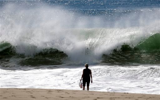 A woman watches the high surf building on the west-facing coast in El Segundo, Calif., on Wednesday, Feb. 24, 2016.