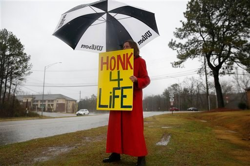 In this photo taken Feb. 22, 2016, Ellie Hermann, stands near the street, protesting the West Alabama Women's Center, in Tuscaloosa, Ala.