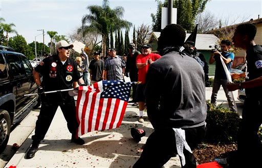 """A Ku Klux Klansman, left, uses an American flag to fend off angry counter protesters after members of the KKK tried to start a """"White Lives Matter"""" rally at Pearson Park in Anaheim, Calif., on Saturday, Feb. 27, 2016."""