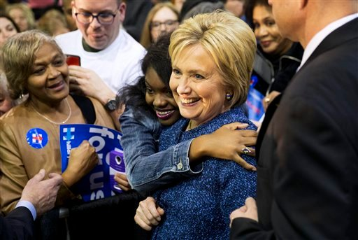 Democratic presidential candidate, Hillary Clinton, right, is embraced by an audience member while posing for a photo at a campaign event at Miles College Saturday, Feb. 27, 2016, in Fairfield, Ala.