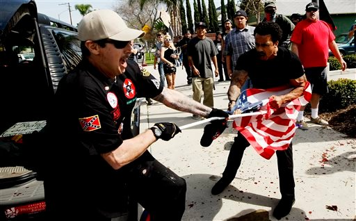 "A Ku Klux Klansman, left, fights a counter protester for an American flag after members of the KKK tried to start a ""White Lives Matter"" rally at Pearson Park in Anaheim on Saturday, Feb. 27, 2016. The event quickly escalated into violence and at least tw"