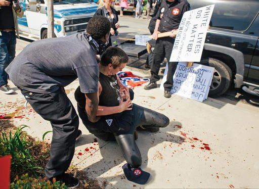 This photo provided by OC Weekly shows counter-protesters scuffling with a KKK member, on the ground, as he stabs an attacking protester, during an anti-immigration rally at Pearson Park in Anaheim on Saturday, Feb. 27, 2016. Three people were stabbed Sat