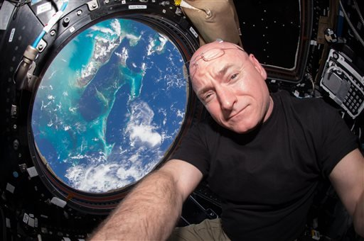 In this July 12, 2015 photo, Astronaut Scott Kelly takes a photo of himself inside the Cupola, a special module of the International Space Station which provides a 360-degree viewing of the Earth and the station. (Scott Kelly/NASA via AP)