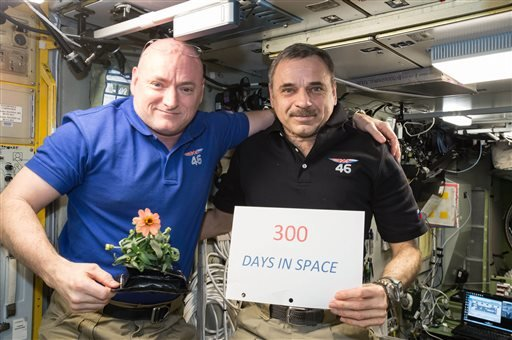 In this Jan. 21, 2016 photo made available by NASA, one-year mission crew members Scott Kelly of NASA, left, and Mikhail Kornienko of Roscosmos celebrate their 300th consecutive day in space. By spending 340 days aboard the International Space Station, th