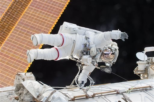 In this Dec. 21, 2015 photo, Expedition 46 Commander Scott Kelly participates in a spacewalk outside the International Space Station in which he and Flight Engineer Tim Kopra, not pictured, moved the station's mobile transporter rail car ahead of the dock