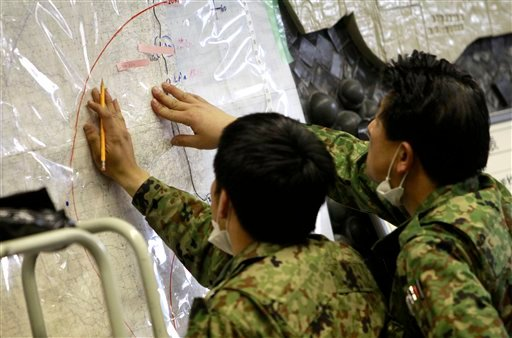 Japan's Defense Ministry officials plot possibly radioactive affected areas on a map at the emergency rescue headquarters monitoring leaked radiation from the Fukushima nuclear facilities damaged by last week's major earthquake and following tsunami.