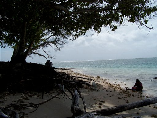 © In this April 25, 2007 file photo, a woman gathers shellfish on an eroded beach on Majuro Atoll in the Marshall Islands.
