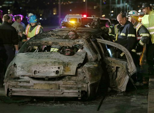 San Mateo County firefighters and California Highway Patrol personnel investigate the scene of a limousine fire on the westbound side of the San Mateo-Hayward Bridge in Foster City, Calif., on Saturday, May 4, 2013.