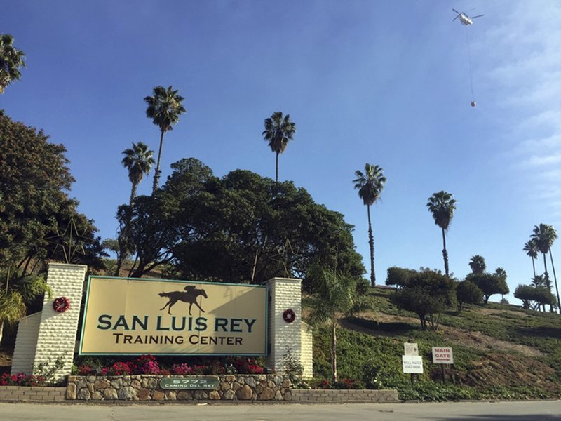 A helicopter prepares to make a water drop over the San Luis Rey Training Center, where thoroughbreds are housed and trained, in Bonsall, Calif., Friday, Dec. 8, 2017.