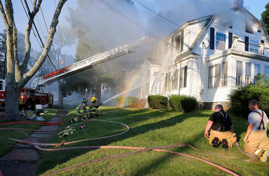 Firefighters battle a house fire in North Andover, Mass., one of multiple emergency crews responding to a series of gas explosions and fires triggered by a problem with a gas line that feeds homes in communities north of Boston. (AP Photo/Mary Schwalm)