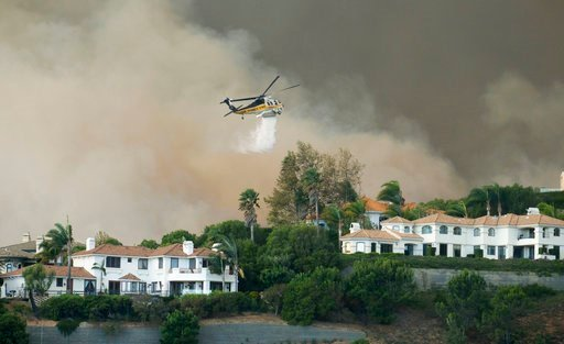 "A helicopter drops water on a brush fire behind homes during the Woolsey Fire in Malibu, Calif., Friday, Nov. 9, 2018. A fast-moving wildfire in Southern California has scorched a historic movie site recently used by the HBO series ""Westworld"" and forced"