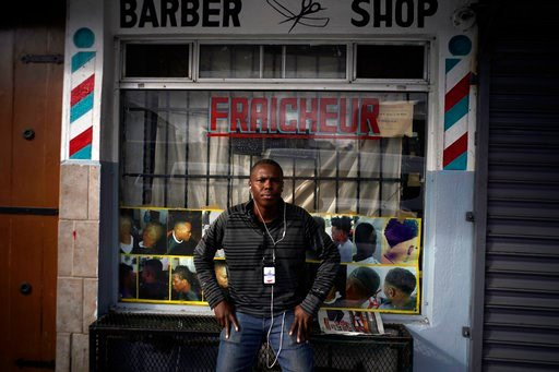 Philocles Julda, 44, poses for a photo in front of a Haitian barbershop in Tijuana, Mexico, Thursday, Nov. 22, 2018. (AP Photo/Ramon Espinosa)