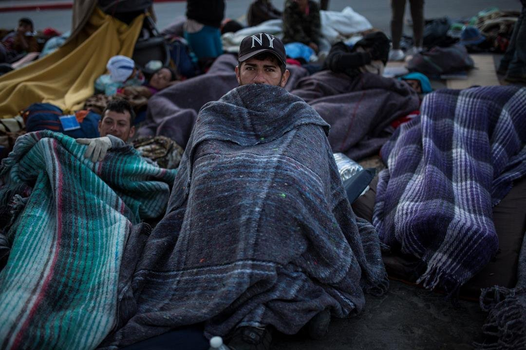 A migrant sits wrapped in a blanket at the Chaparral border crossing in Tijuana, Mexico, Friday early morning, Nov. 23, 2018. (AP Photo/Rodrigo Abd)