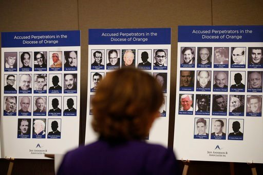 An advocate and survivor of sexual abuse, looks at the photos of Catholic priests accused of sexual misconduct by victims during a news conference Thursday, Dec. 6, 2018, in Orange, Calif.  (AP Photo/Jae C. Hong)